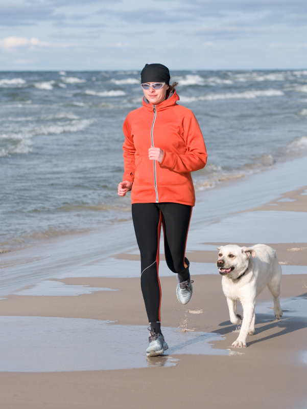 running with dog on beach
